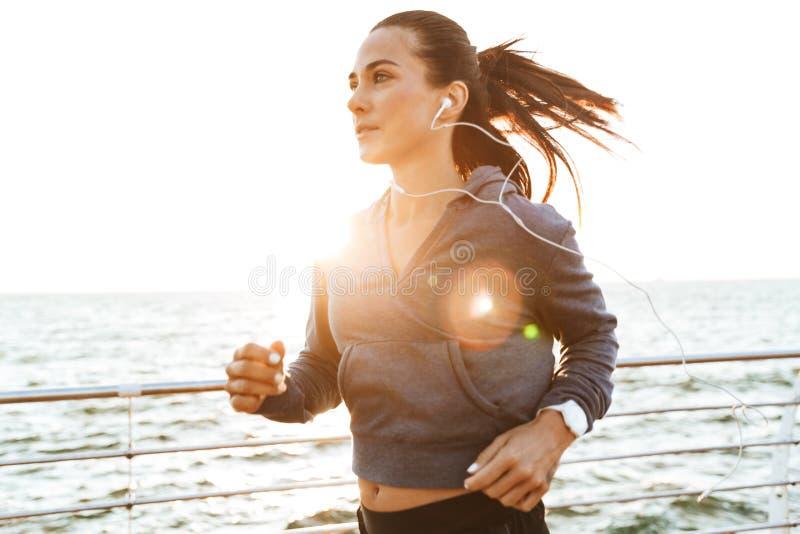 跑在海滩的年轻体育健身妇女户外 免版税库存照片