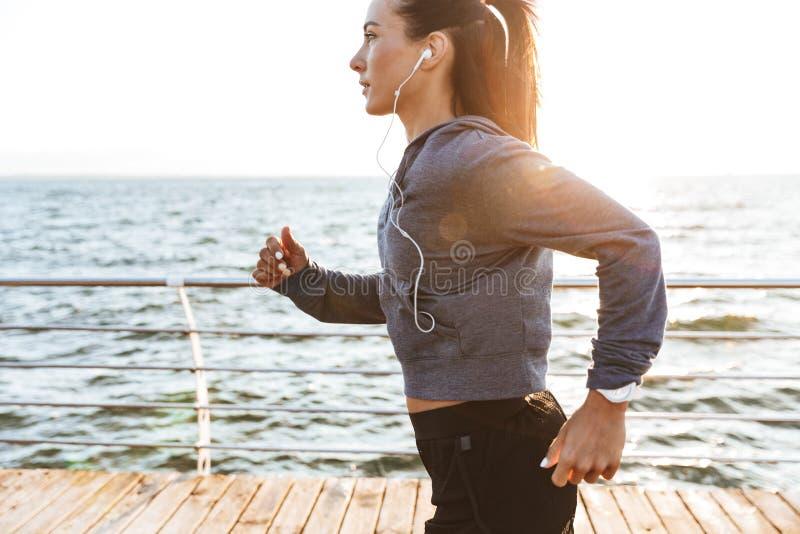跑在海滩的年轻体育健身妇女户外 库存图片