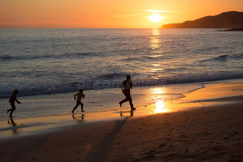 跑在海滩的父亲和孩子在日落,普腊亚da卢斯,葡萄牙期间 库存图片