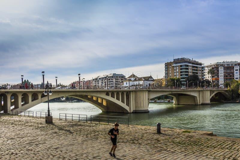 跑步沿运河阿方索十二世的一个人在圣特尔莫桥梁以后 库存照片