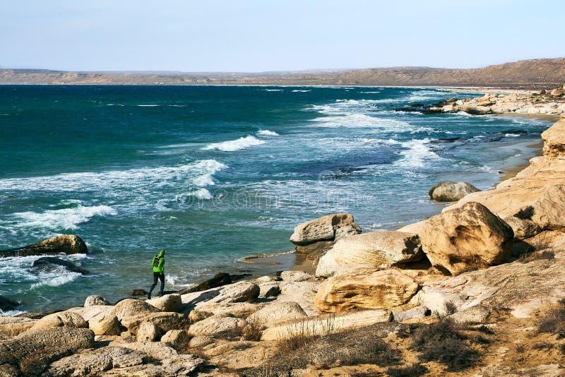 跑沿海滨的特雷伊 一个人沿在石头中的海滨跑在一好日子 免版税图库摄影