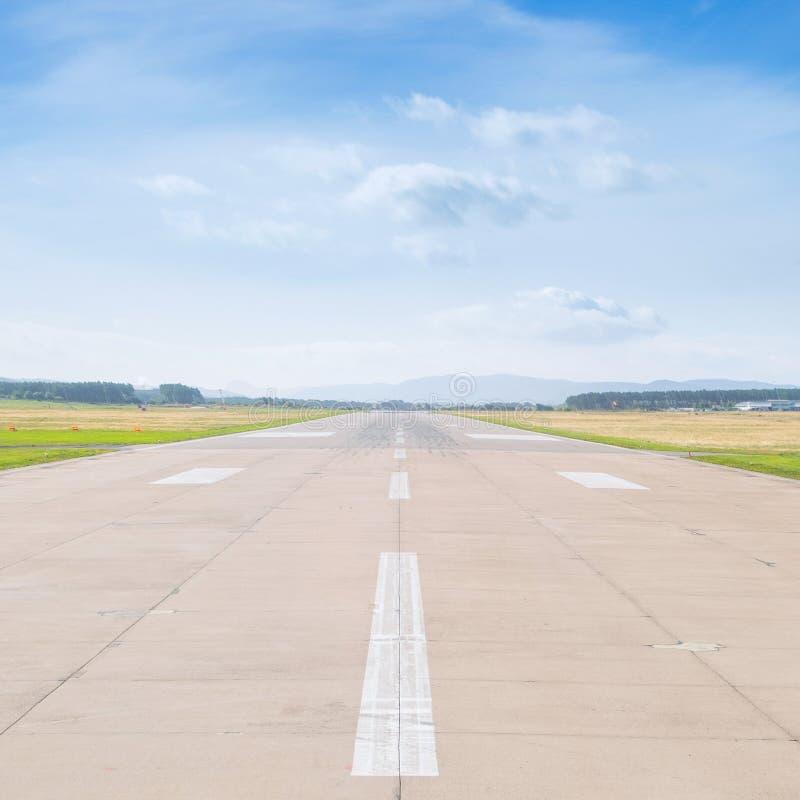 跑道在机场在与云彩的晴朗的夏天中午12点 免版税图库摄影