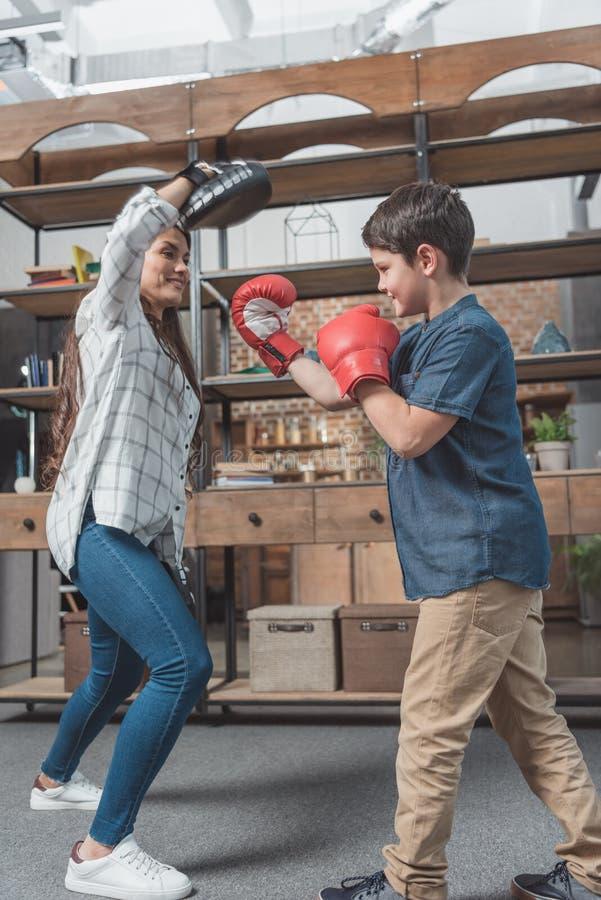 踢一个猛击的垫的拳击手套的小男孩举行由他的母亲 免版税库存图片