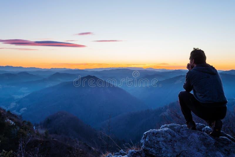 蹲下在小山观看的暮色风景顶部的男性徒步旅行者在日落以后 图库摄影