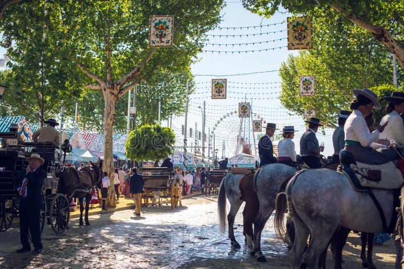 车手和人们在传统服装穿戴了享受4月市场 塞维利亚整整的宗教节日de塞维利亚 库存图片