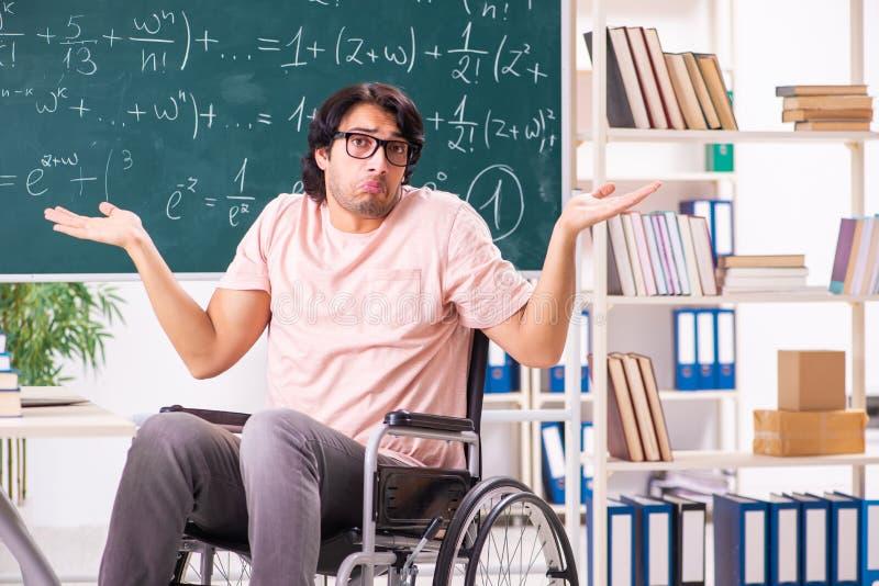 轮椅的年轻帅哥在黑板前面 库存图片