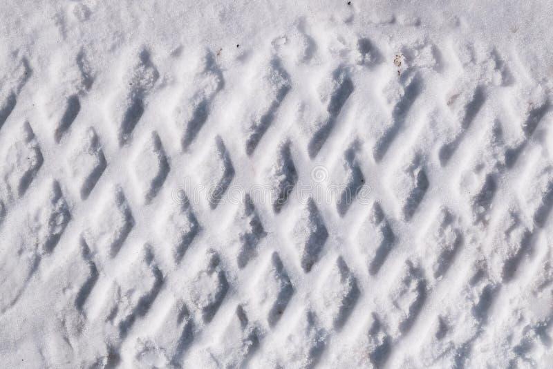 轮胎踪影在雪的 纹理,积雪的表面背景 免版税库存图片