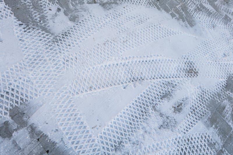 轮胎踪影在雪的 纹理,积雪的表面背景 免版税库存照片