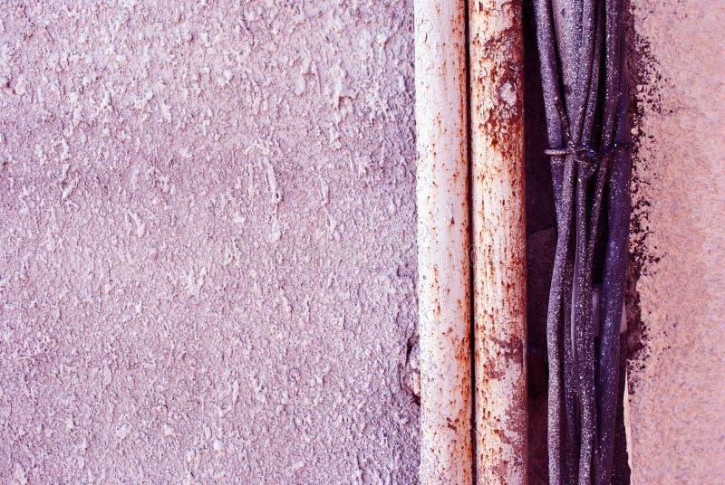 软的桃红色灰色颜色织地不很细墙壁、油漆或者膏药下落在墙壁表面关闭的与管子和黑电缆的细节 库存图片