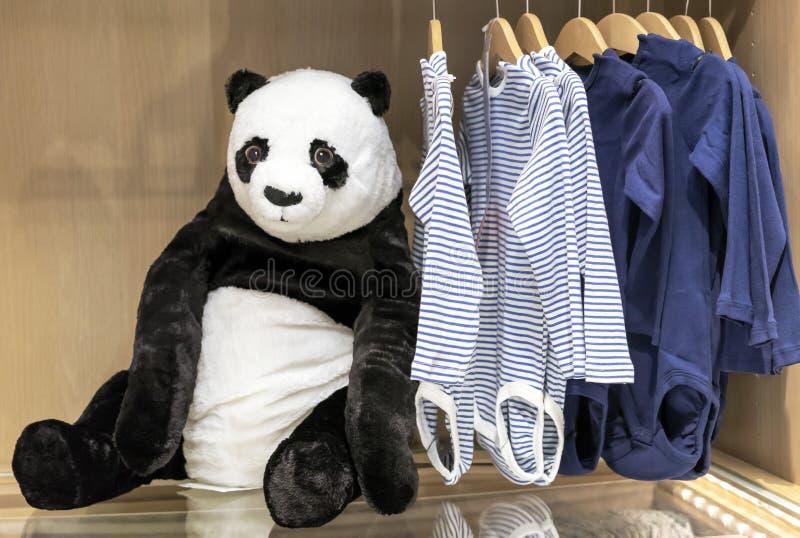 软的玩具熊猫涉及儿童的衣物背景  免版税库存图片