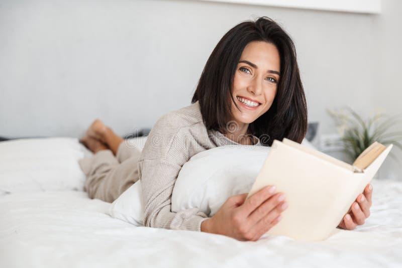 轻松的妇女30s看书照片,当在家时在与白色亚麻布的床上 免版税库存照片