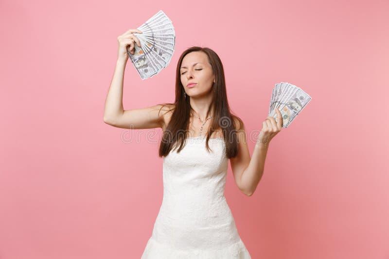 轻松的新娘妇女画象有闭合的眼睛的在白色婚纱藏品捆绑许多美元,现金金钱 免版税库存照片