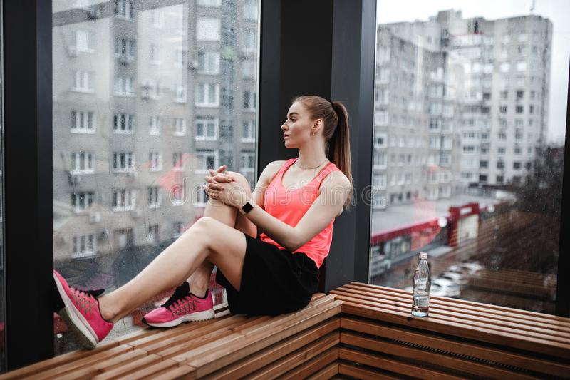 运动女孩穿戴了体育短裤,并且T恤杉坐在现代健身房的木窗台 免版税库存图片