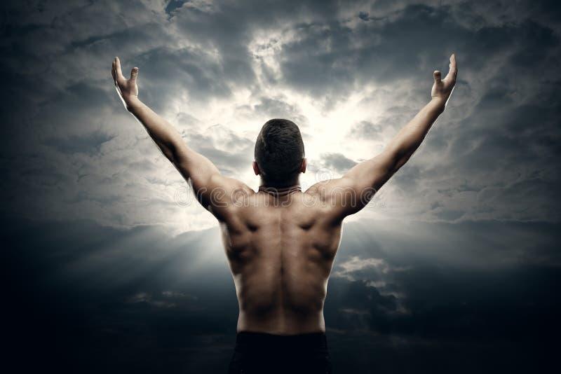 运动在日出天空,肌肉运动员身体后面景色的人开放胳膊 免版税图库摄影