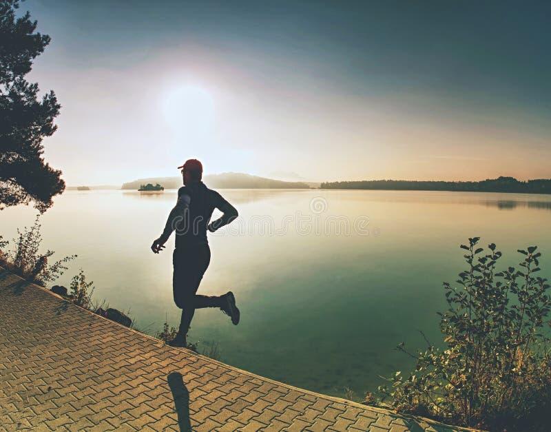运动员奔跑剪影在日落背景拷贝空间的 图库摄影
