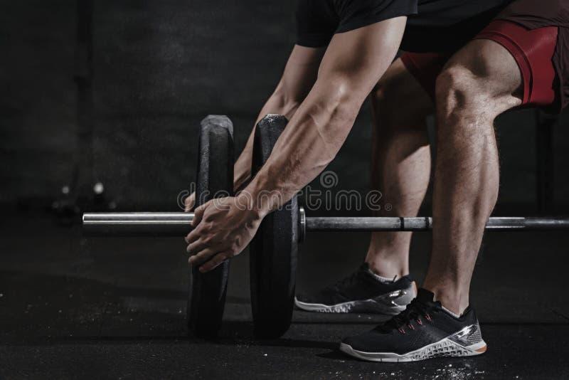 运动员特写镜头为举的重量做准备在crossfit健身房 杠铃氧化镁保护 实践的功能训练p 库存图片