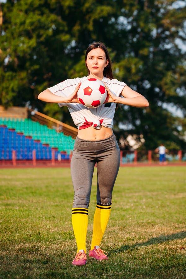 运动服的美丽的年轻运动妇女在有橄榄球球的体育场内训练 拿着球 库存图片