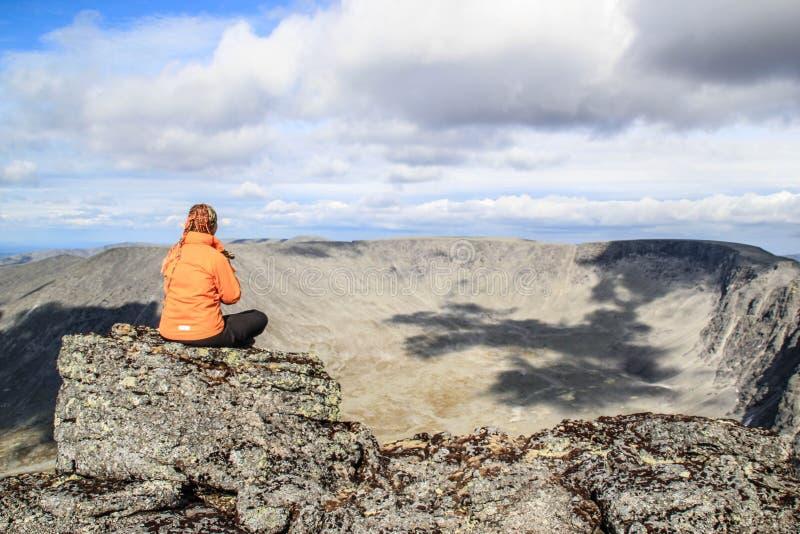 运动服的白白种人女孩游人坐岩石在山顶部 库存图片