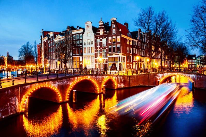运河和桥梁夜视图在阿姆斯特丹,荷兰 免版税库存照片