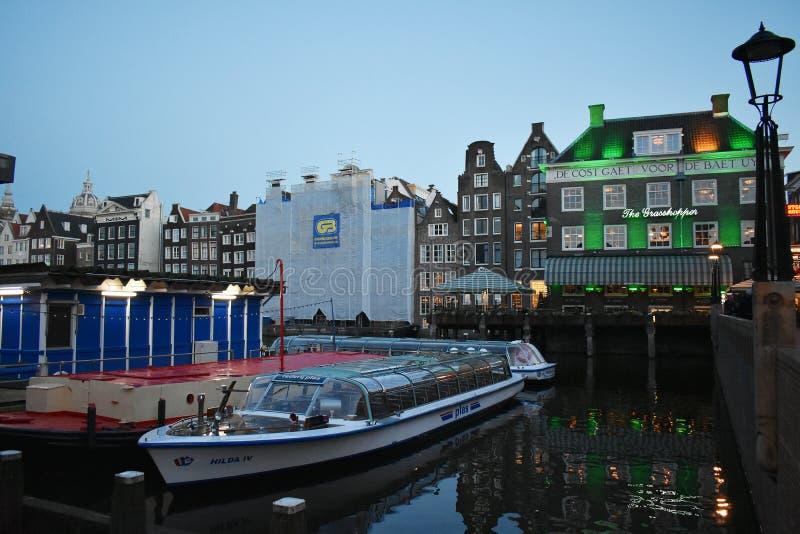 运河船在阿姆斯特丹运河巡航离开地方  免版税图库摄影