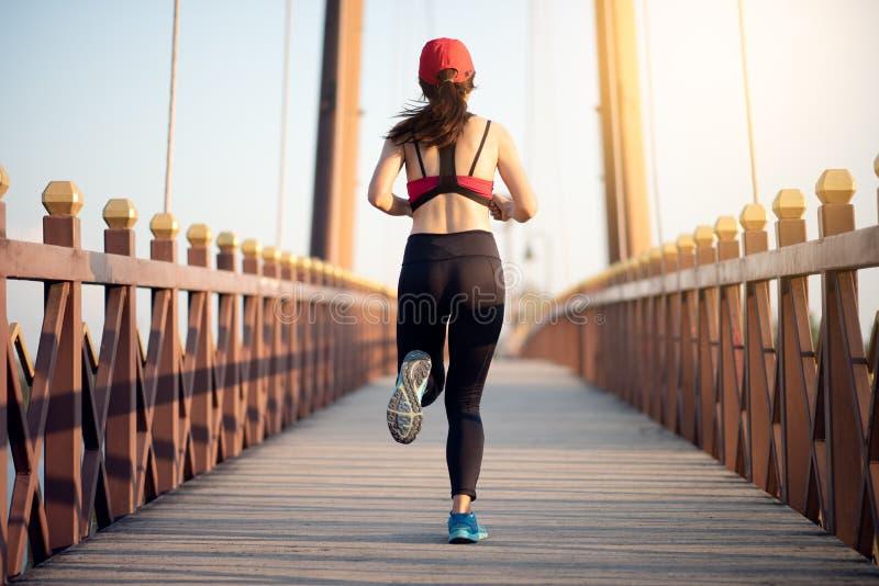 运行在桥梁的幼小亚洲妇女赛跑者早晨 免版税库存照片