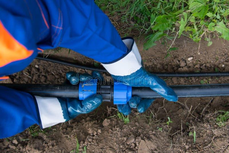 运转的手,特写镜头,检查聚丙烯管子的正确连接,连接在被挖掘的沟槽的水 库存照片
