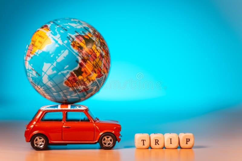 运载世界地图气球和旅行词的微型玩具葡萄酒汽车 旅行和运输概念 库存图片