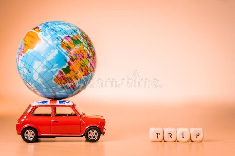 运载世界地图气球和旅行词的微型玩具葡萄酒汽车 旅行和运输概念 免版税库存照片