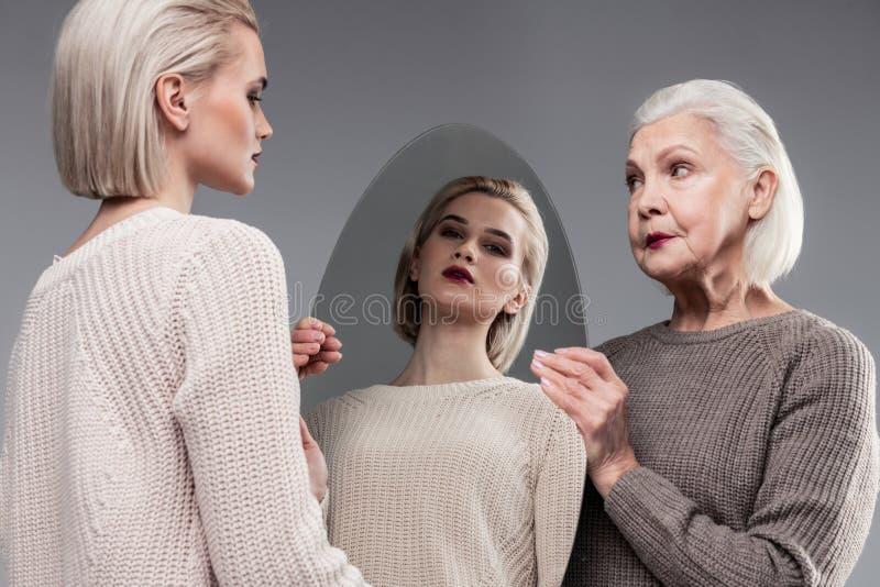 运载卵形镜子的严肃的短发老妇人,当她女儿观察时 库存图片