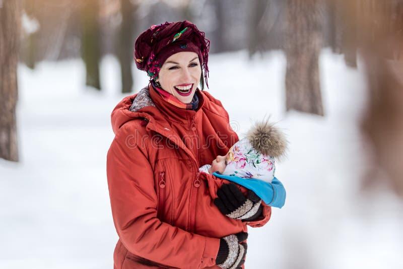 运载她的女婴的母亲佩带红色夹克和吊索 免版税库存照片