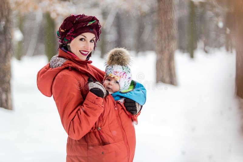 运载她的女婴的母亲佩带红色夹克和吊索 免版税库存图片