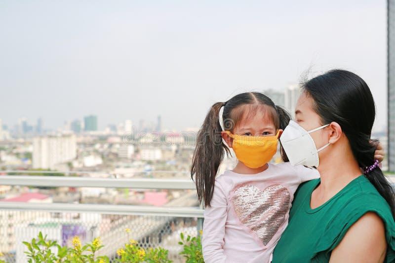 运载她的有戴着的亚裔母亲保护面具女儿反对PM 2 5空气污染在曼谷市 泰国 库存图片