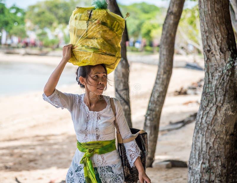 运载巴厘语的妇女保佑在她的头的canang盘子 免版税库存图片