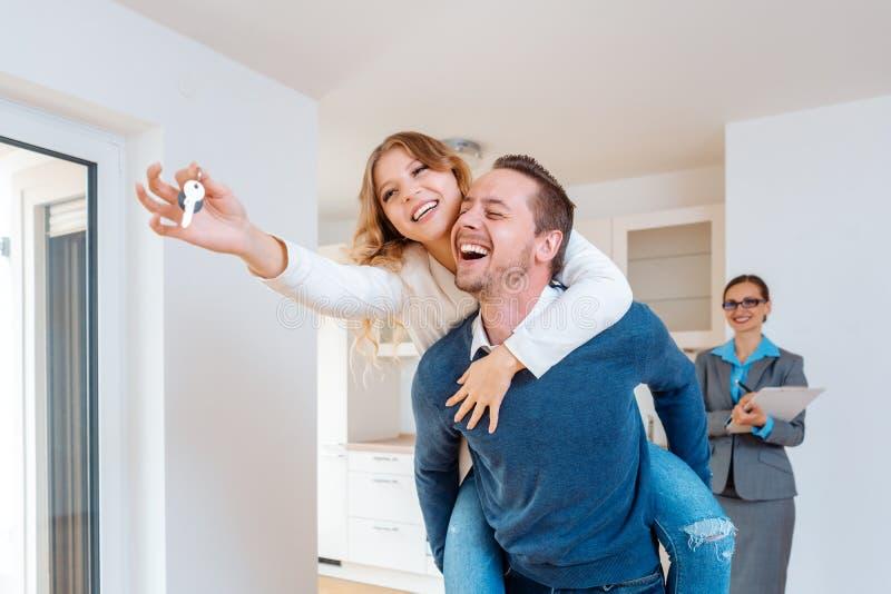 运载显示房子钥匙的他的妻子肩扛的人 免版税库存照片