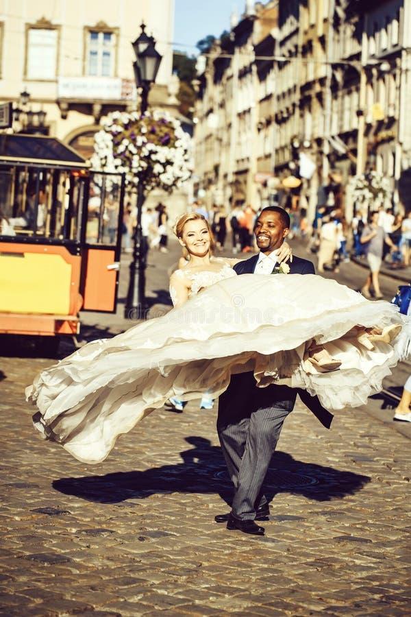 运载胳膊的愉快的非裔美国人的新郎逗人喜爱的新娘 免版税库存照片