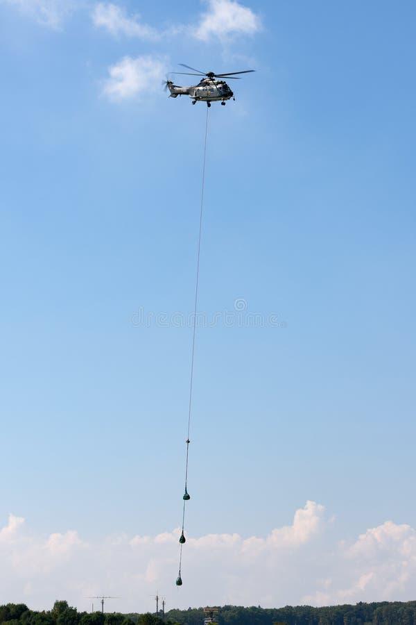 运载货物的吊索装载在长行的瑞士空军队法国航太公司AS332 TH89军用公共直升机T-320 免版税图库摄影