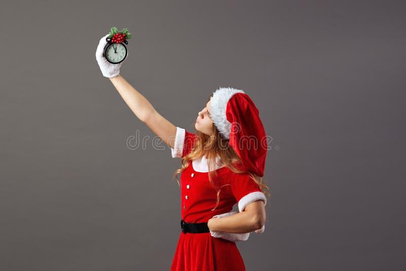 迷人的夫人 在红色长袍、圣诞老人的帽子和白色手套穿戴的圣诞老人项目拿着显示五的一个时钟 库存照片