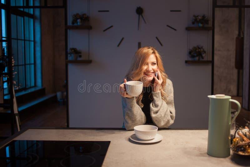 迷人的女孩在厨房里在早晨 谈话在电话和有有杯子的早餐A年轻女人在她的手上 免版税库存照片