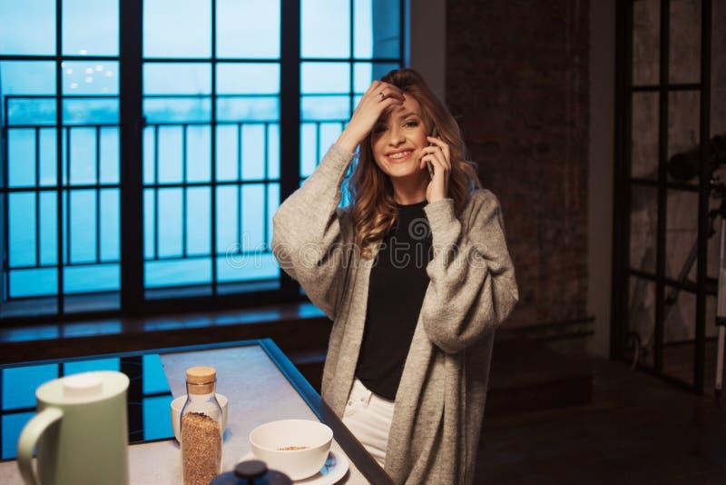 迷人的女孩在厨房里在早晨 谈话在电话和有有杯子的早餐A年轻女人在她的手上 图库摄影