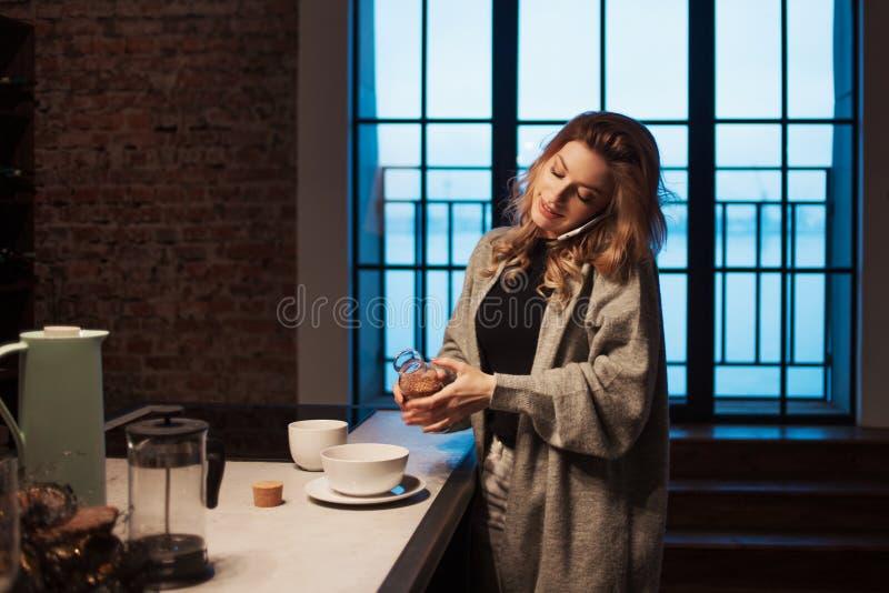 迷人的女孩在厨房里在早晨 谈话在电话和有有杯子的早餐A年轻女人在她的手上 库存照片