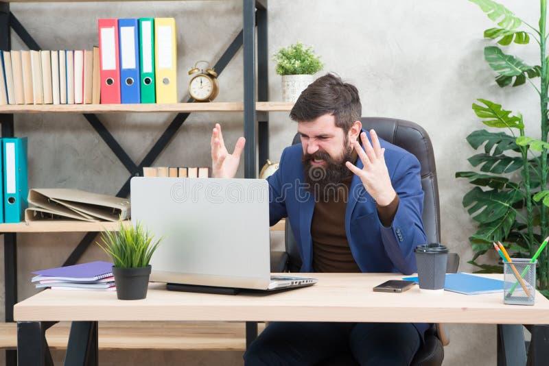 进入混乱 人有胡子的上司经理坐有膝上型计算机的办公室 在网上解决业务问题的经理 在白色的背景商业查出的人 免版税库存图片