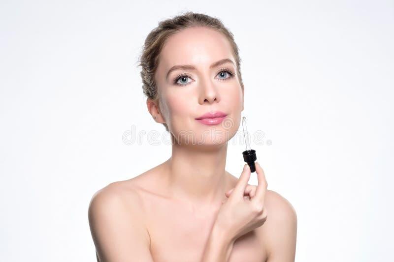 进行在白色的美好的模型一种化妆皮肤血清治疗 库存图片