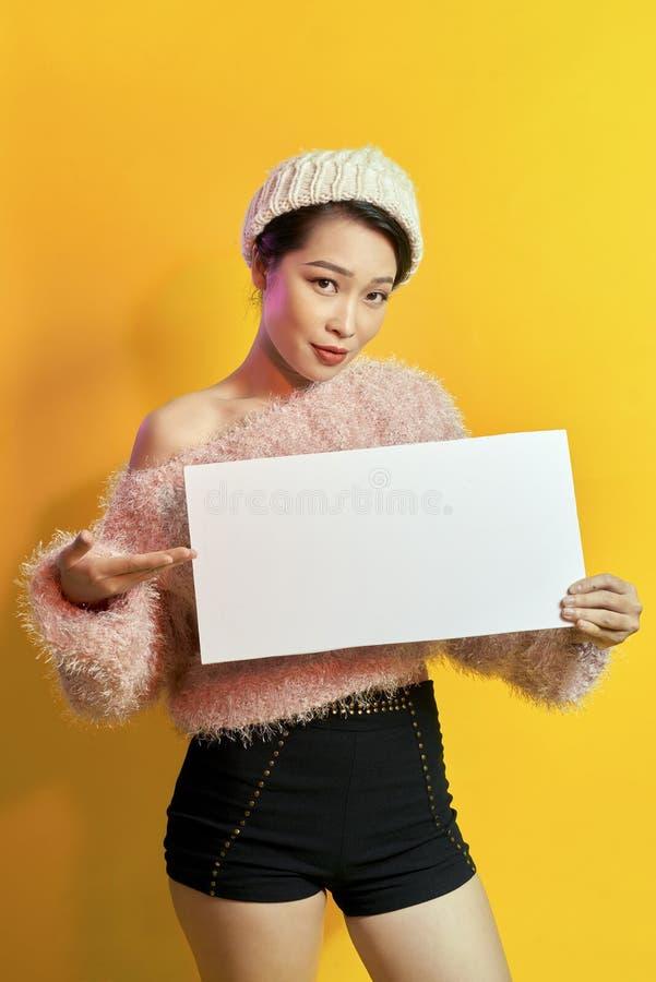 这里您的文本 相当拿着空的空白的委员会的年轻激动的妇女 五颜六色的演播室画象有黄色背景 免版税库存照片
