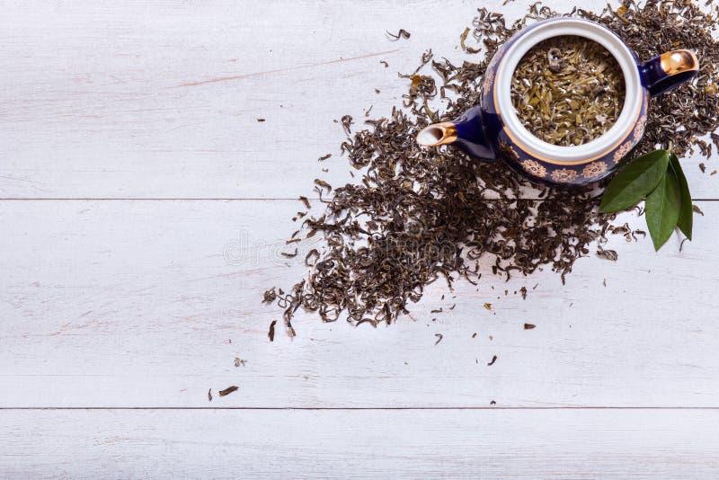 茶壶和干茶叶在白色木背景,绿色茶叶在桌,黑草本自创热的饮料上在瓷 免版税库存照片