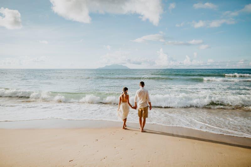 蜜月在海滩的婚礼夫妇在日落 免版税库存照片