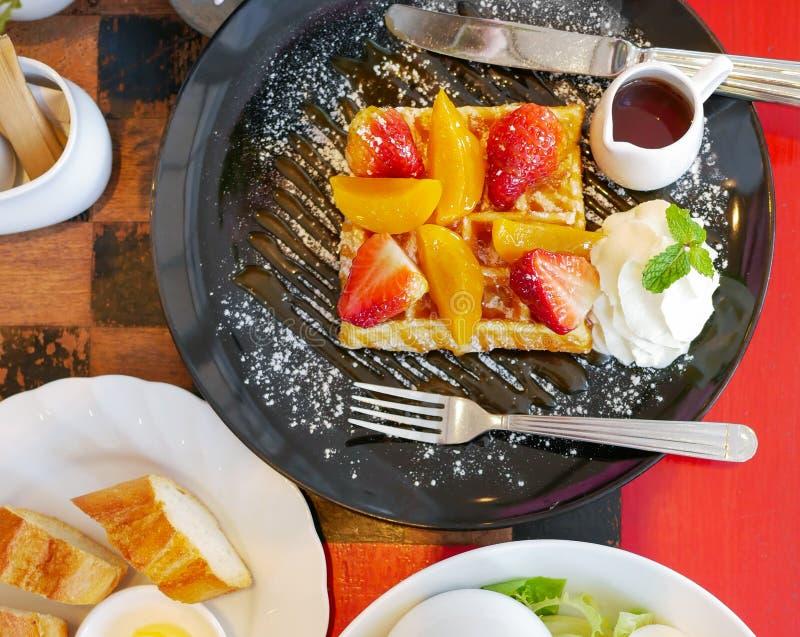 蜂蜜奶蛋烘饼顶视图用草莓和桃子和结冰在红色桌背景的黑色的盘子洒 免版税库存图片