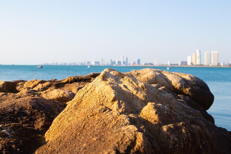 芭达亚泰国,海岸线,岩石岸,沿海,大厦,与白色好的天空蔚蓝的散步全景  免版税库存照片