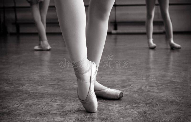 芭蕾舞女演员脚特写镜头在pointe鞋子的在舞厅里 葡萄酒摄影 一位芭蕾舞女演员的特写镜头在舞厅里 库存图片