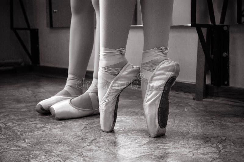 芭蕾舞女演员脚特写镜头在pointe鞋子的在舞厅里 葡萄酒摄影 一位芭蕾舞女演员的特写镜头在舞厅里 免版税库存照片