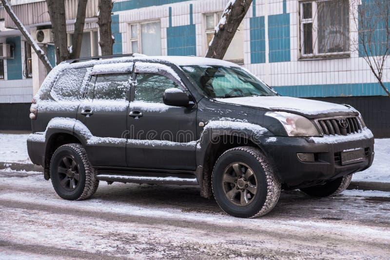 莫斯科,俄罗斯,11月,28日 2018年:在一条大城市街道上的被放弃的积雪的汽车丰田陆地巡洋舰 降雪的后果 库存照片